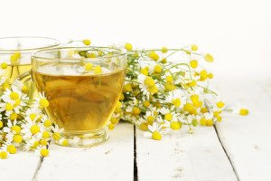39909231 - cup of chamomile tea with chamomile flowers on white wooden planks